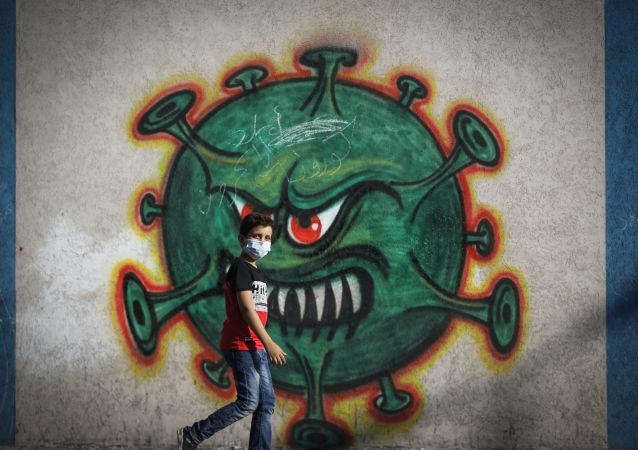 加沙一名男孩走過畫著新冠病毒的塗鴉牆