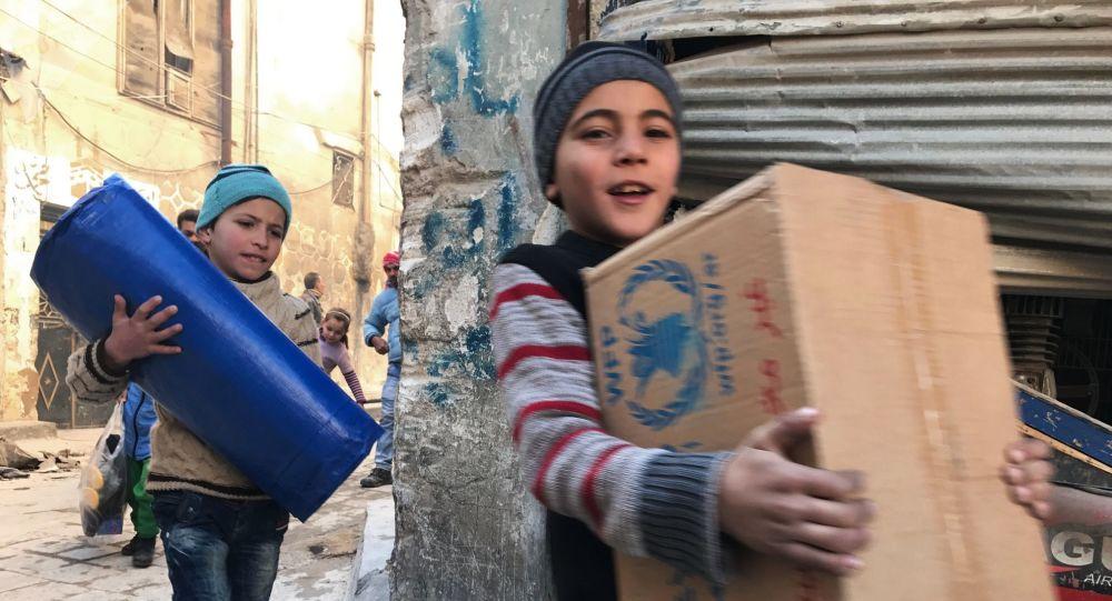 俄军人在叙利亚塔尔图斯省分发食品包