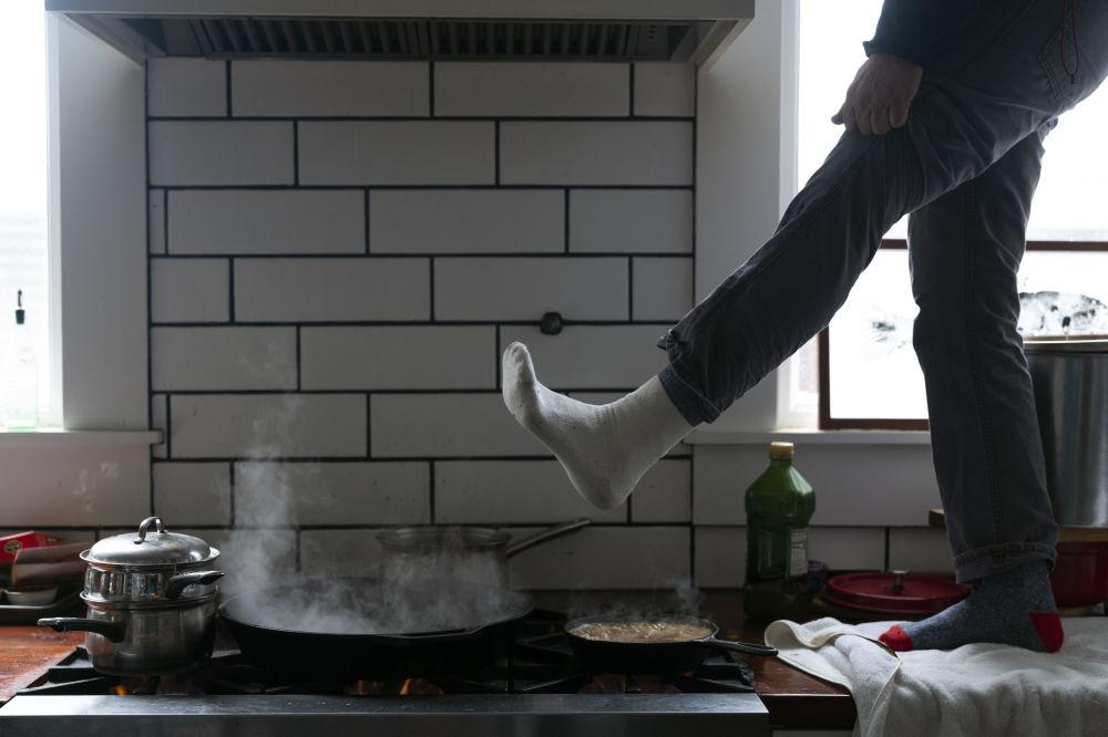 得州奥斯汀,一名男子在煤气炉上暖脚。