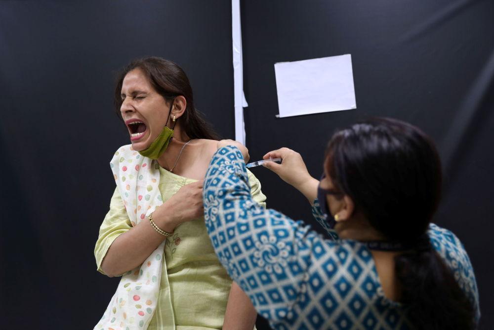 """印度血清研究所为居民接种阿斯利康公司""""CoviShield""""疫苗。"""
