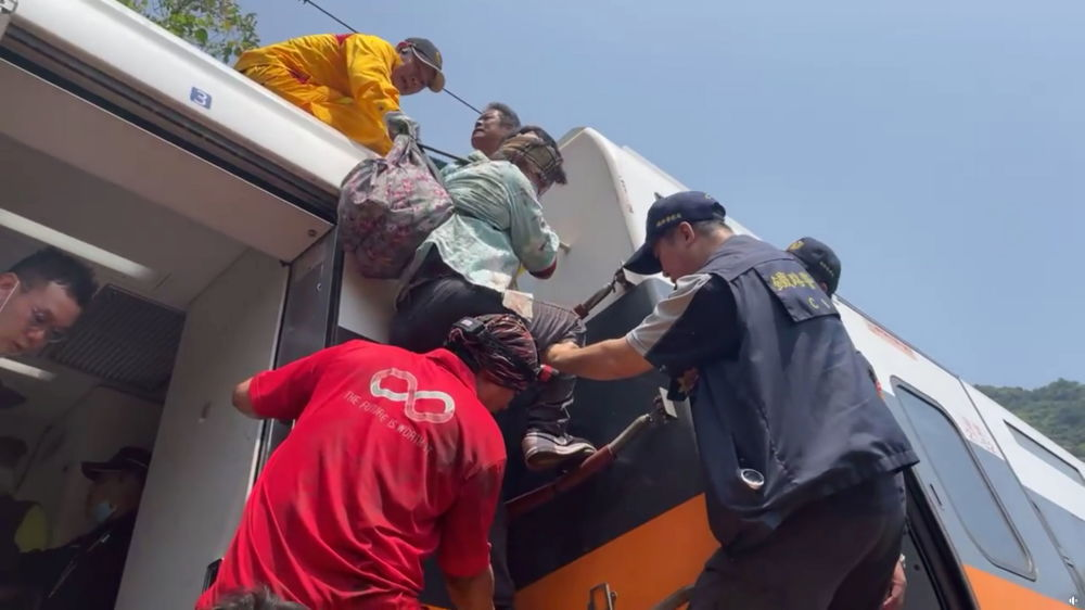 救援人員救助受傷乘客。