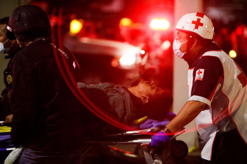 救援人员用担架抬着在Olivos和Tesonko车站区域发生轨道交通桥梁坍塌事故的伤者