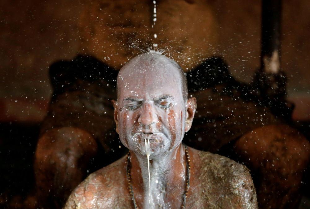 度民眾阿碩克•奧扎用牛奶清洗全身塗抹的聖物牛糞。