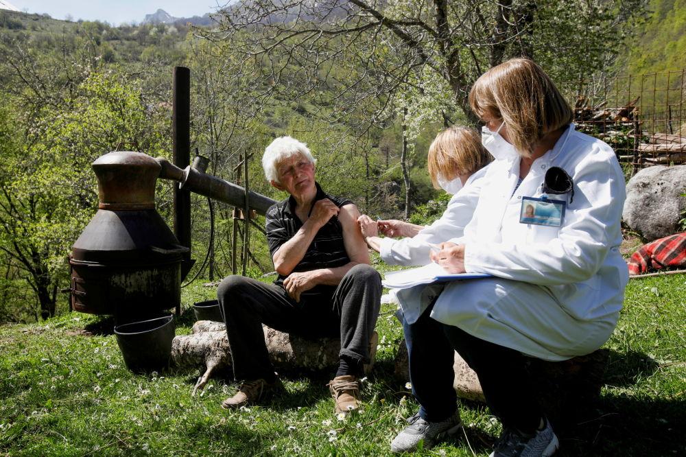 黑山莱维斯塔村,一名男子在一罐白兰地旁接种新冠疫苗。