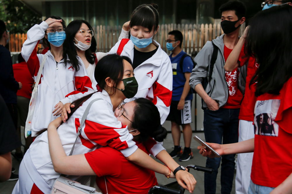 北京考生在考场外相互拥抱,鼓励好友高考顺利。