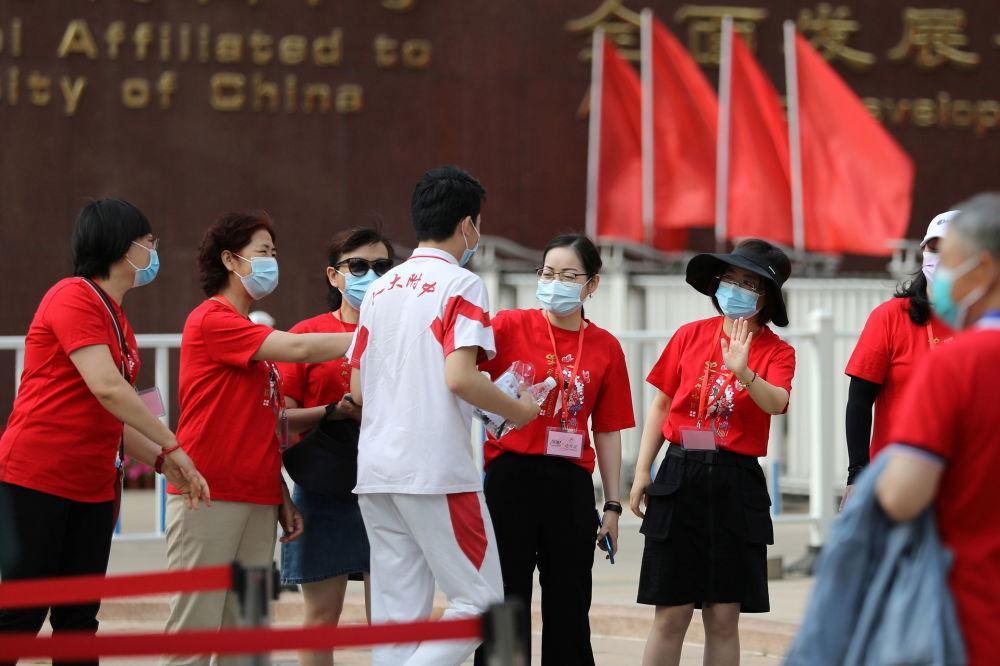 北京某中学教师们为参加高考的同学加油助威。