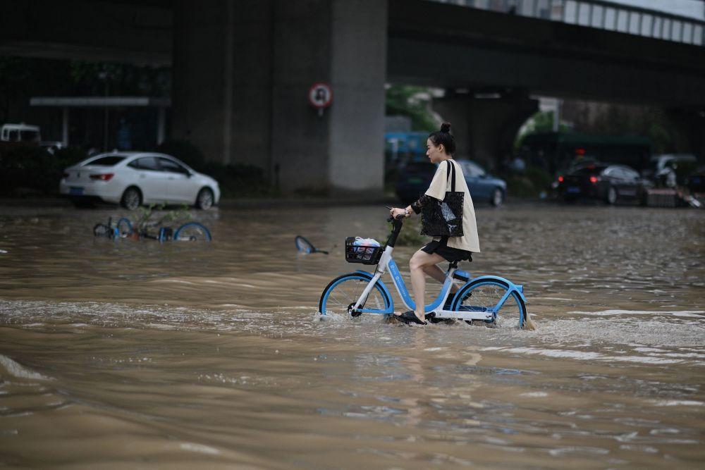 河南居民在大水淹没的街道上骑行。