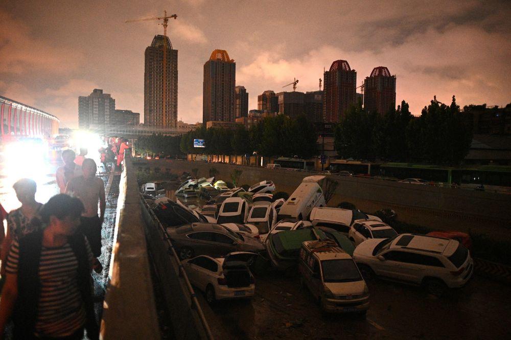 河南居民在交通隧道前观察受损车辆。