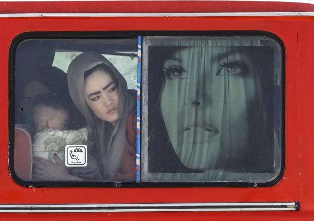 伊朗-阿富汗边境的一辆公共汽车上,一名抱着孩子的阿富汗妇女。