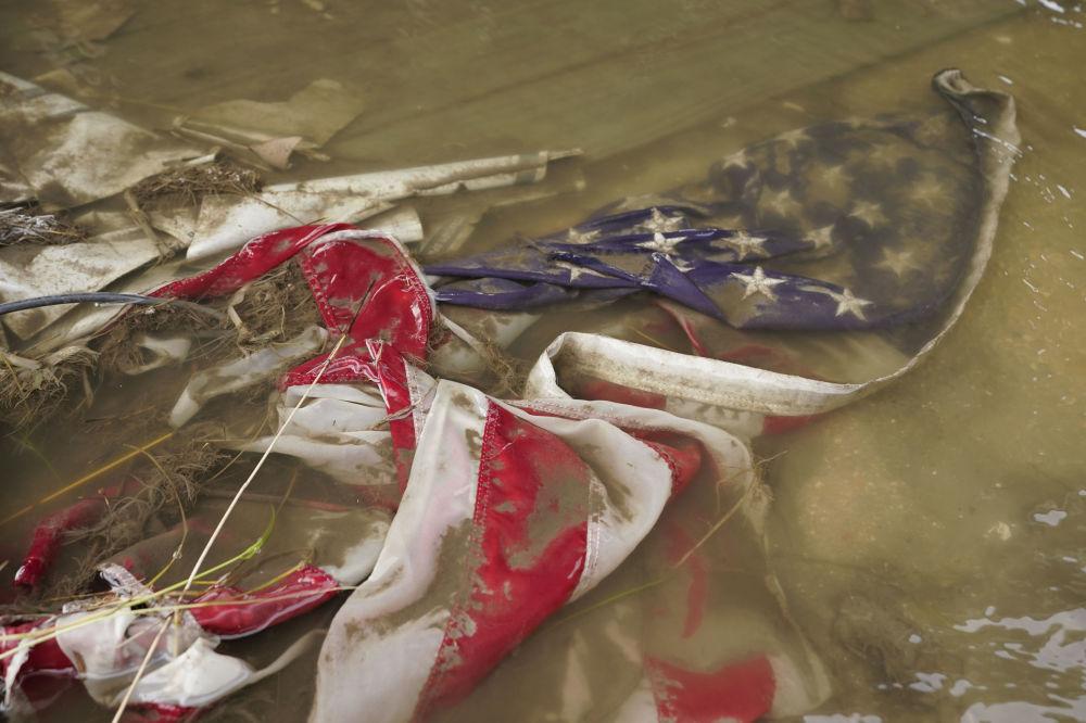 """被飓风""""艾达""""吹进水潭的一面美国国旗。"""
