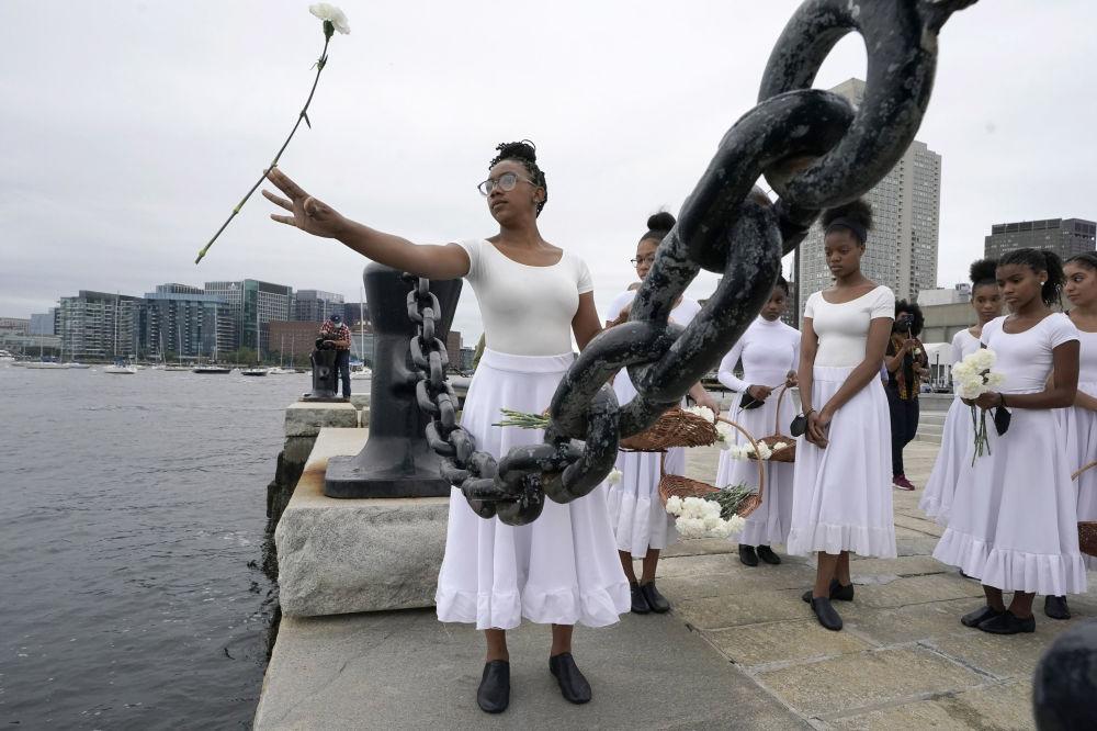美国OrigiNation文化中心的Girlz of Imani舞蹈团演员将鲜花抛入波士顿港。当天,波士顿港举行承认奴隶制海港悼念仪式。