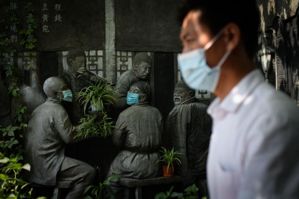 一位佩戴口罩的北京市民路过一处雕塑。