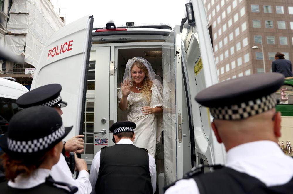 """""""反抗灭绝""""抗议者身着婚纱占领伦敦警车。"""
