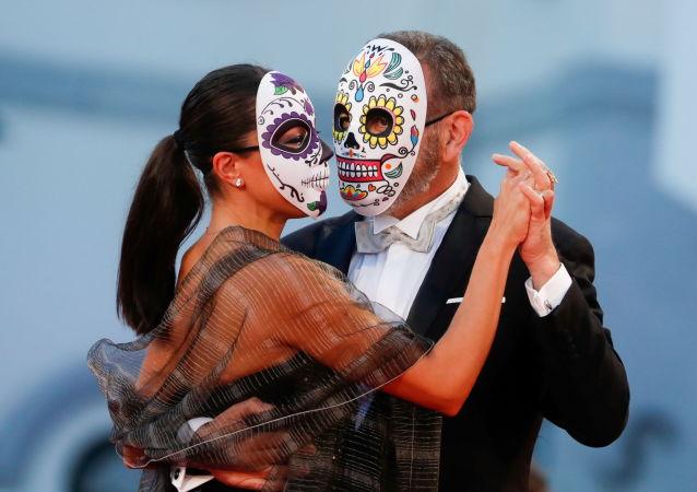演员埃尔南•门多萨与女友佩戴面具参加第78届威尼斯国际电影节开幕式。