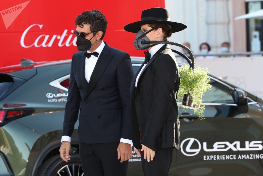 女影星芭芭拉•帕斯(图右)佩戴氧气面罩参加第78届威尼斯国际电影节开幕式。