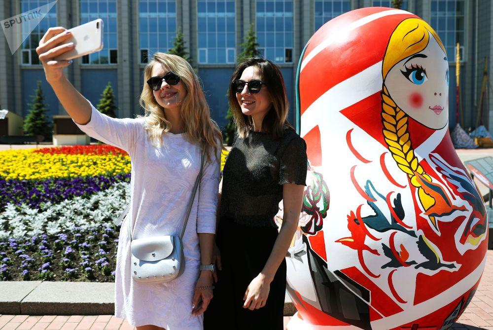 萨马拉河岸边,姑娘们在艺术家为2018年俄罗斯世界杯绘制的套娃旁边拍照留念。