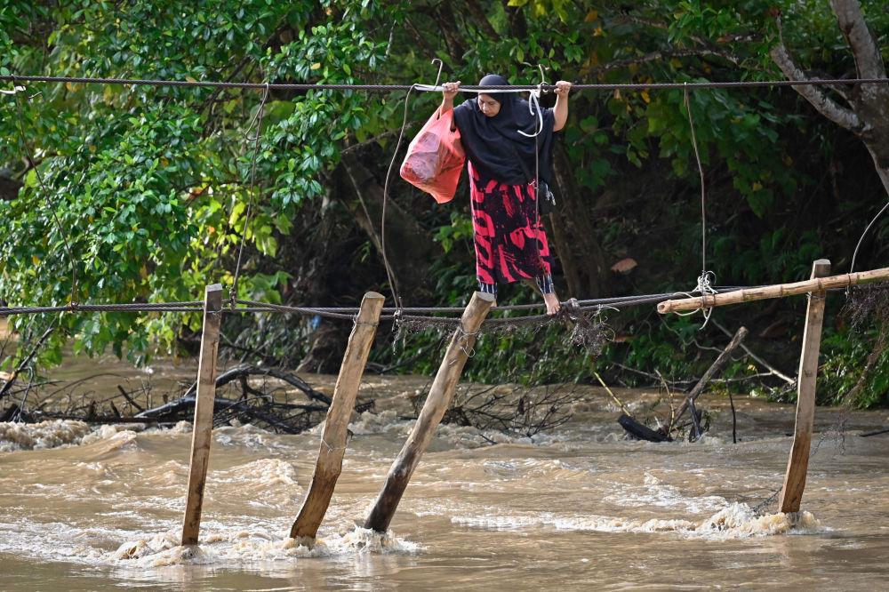 一女子通过一座被洪水冲垮的桥,印尼南苏拉威西省