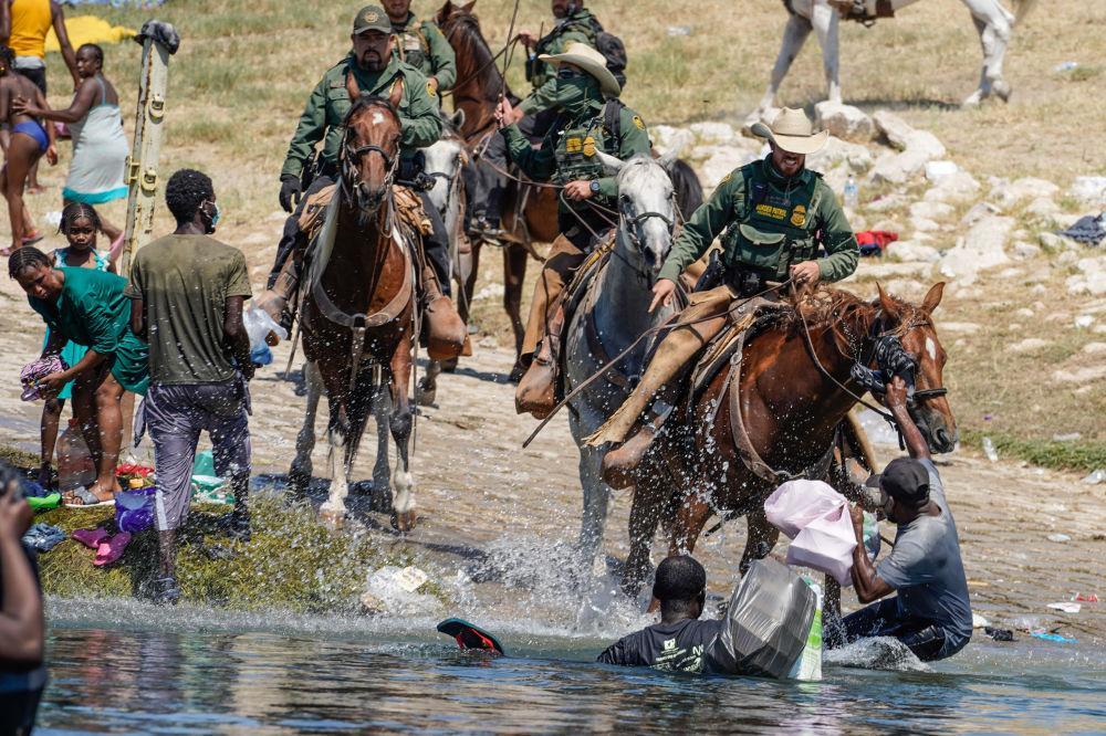 美国边境巡逻队试图阻止海地移民进入德克萨斯州德尔里奥市格兰德河岸营地。