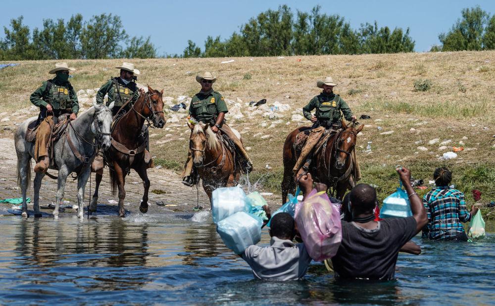 美国边境骑警试图阻止海地移民进入德克萨斯州德尔里奥市格兰德河岸营地。