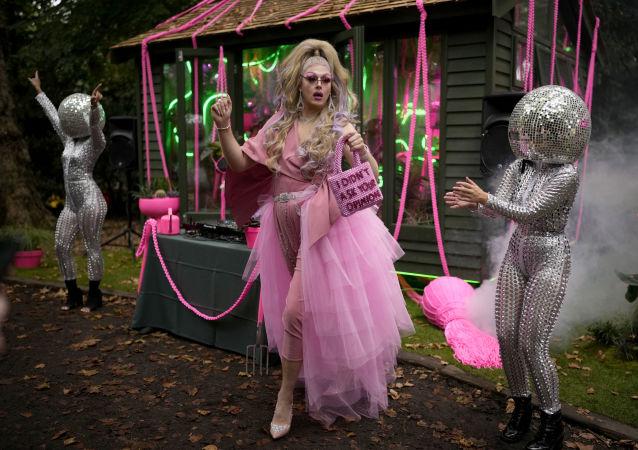 身着女王服装的女园丁在鲜花展上与表演者们共舞,伦敦切尔西