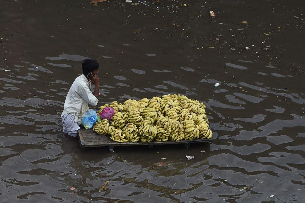 一場大雨後,街上推著推車的賣水果的商販被困在水中,巴基斯坦拉合爾