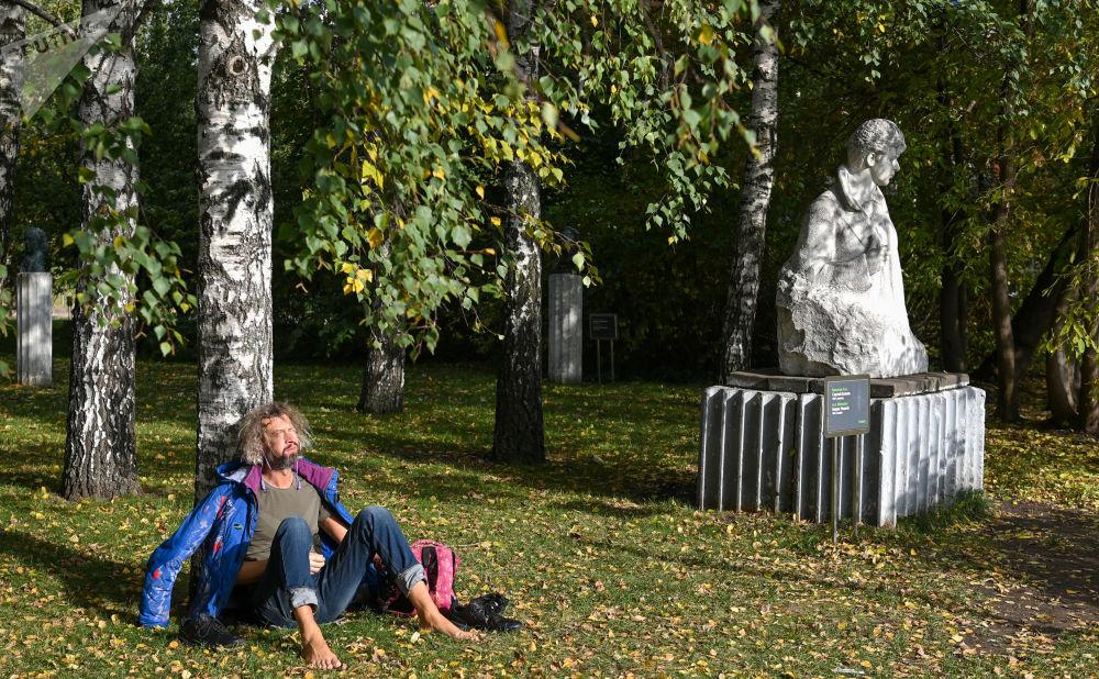 一名男子坐在莫斯科Muzeon艺术公园的树下晒太阳。