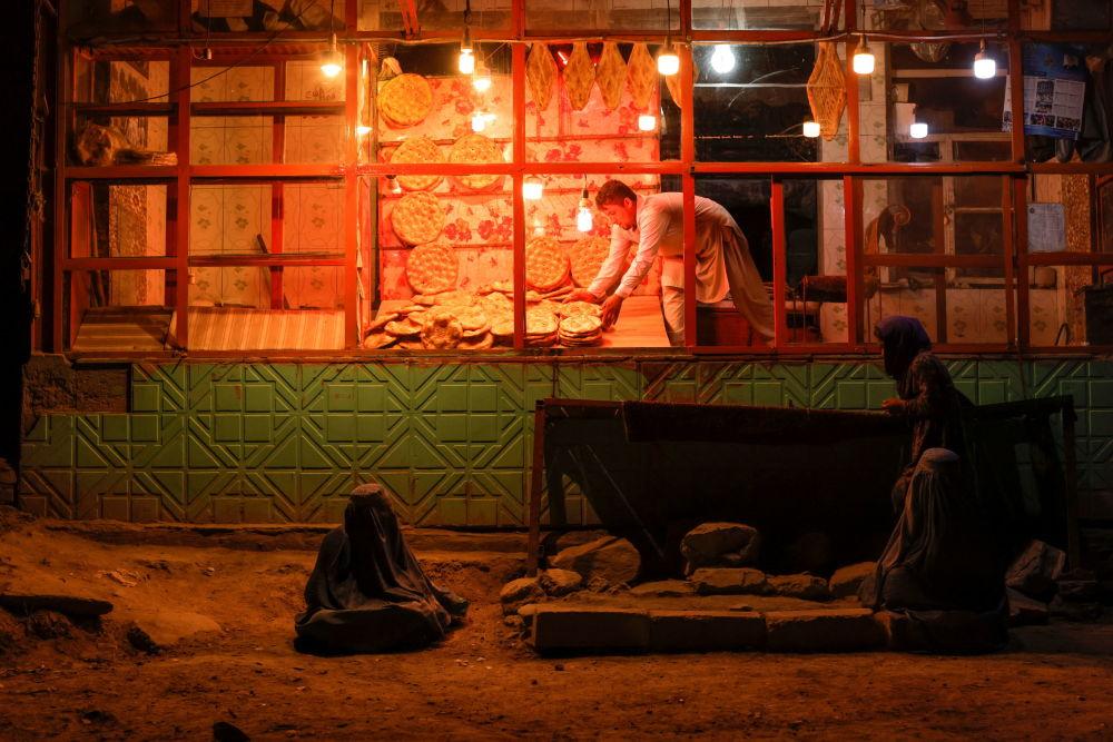 喀布尔一家面包房附近身着布尔卡长袍的女子。