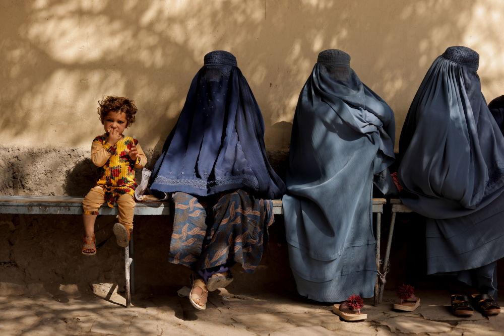 喀布尔一家医院附近,一个小女孩和几个身着布尔卡长袍的女子坐在一起。