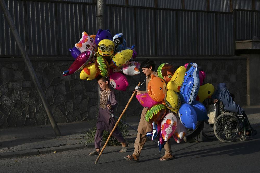 喀布尔街上卖气球的孩子。