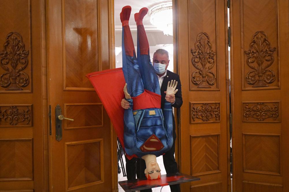 布加勒斯特罗马尼亚议会,一名男子手持超人形象的假人。
