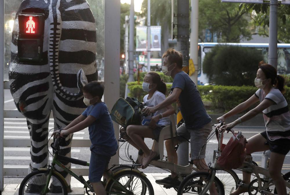 台湾台北,斑马形红绿灯旁戴口罩骑自行车的人们。