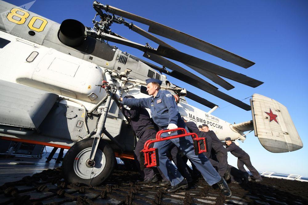 """俄中 """"海上联合-2021"""" 海上军演在日本海水域举行。图为俄海军""""轰鸣""""号护卫舰水兵正在推移卡-27PS直升机入库。"""
