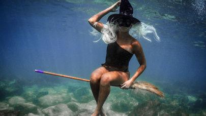 身着万圣节服饰的黎巴嫩女潜水者在水下拍照。