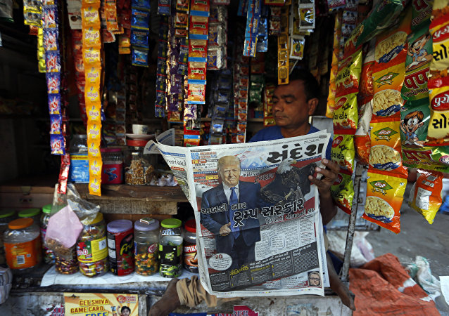 Indian vendor who sells snacks and chewable tobacco reads a Gujarati language newspaper that has the headline this time Trump Government