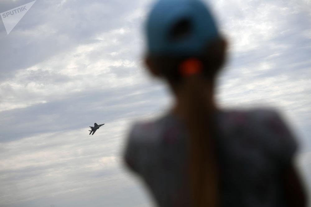 一个女孩正在观看其中一架参展飞机进行飞行训练。