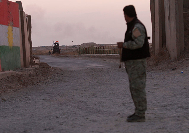 A Kurdish Peshmerga fighter looks at the Shi'ite Popular Mobilization Forces (PMF) in the Southwest of Kirkuk, Iraq