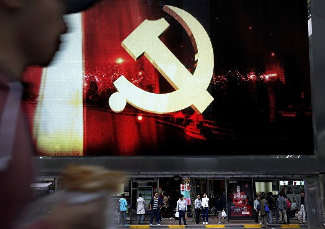 A man walks by an advertising electric panel showing the Communist Party logo