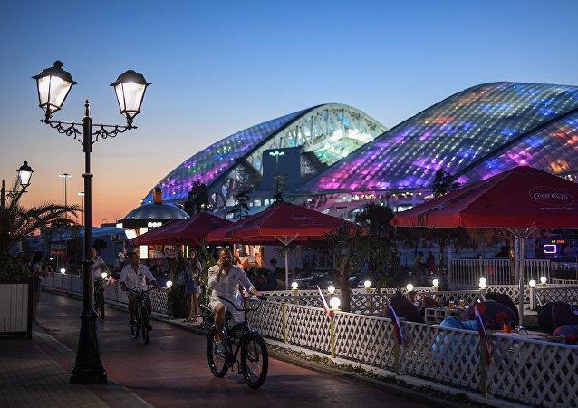 Туристы едут на велосипедах по набережной в Сочи в районе Олимпийского парка