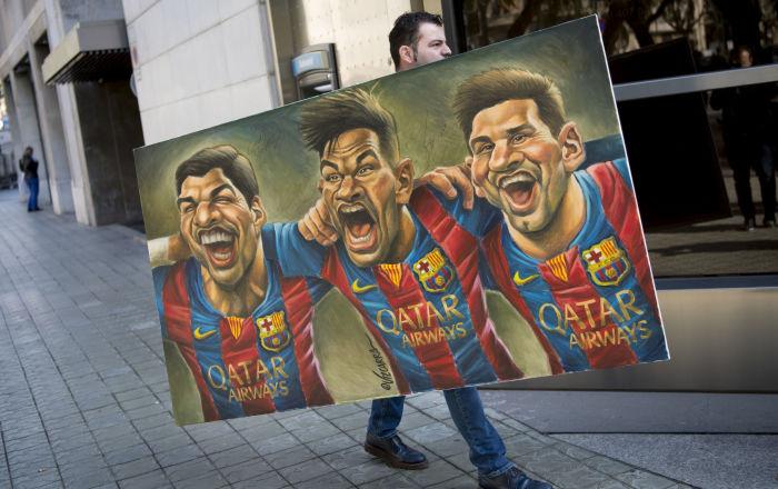 一名男子拿著漫畫家Vizcarra的畫,上面畫著球星蘇亞雷斯、內馬爾、梅西等人。