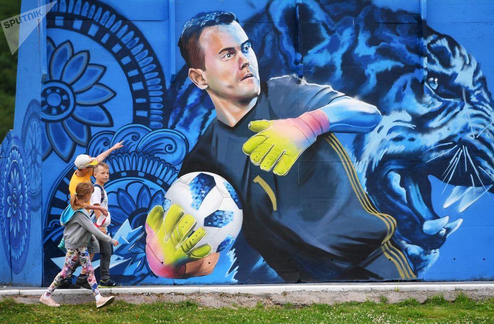 孩子们在看画着俄罗斯国家足球队守门员伊戈尔·阿金费耶夫的涂鸦。