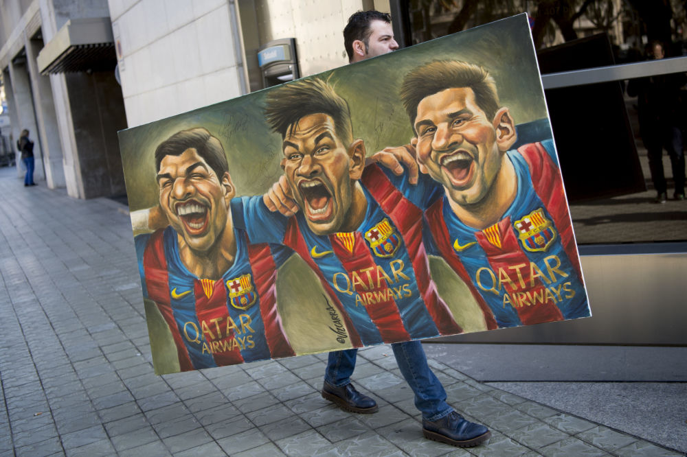 一名男子拿着漫画家Vizcarra的画,上面画着球星苏亚雷斯、内马尔、梅西等人。