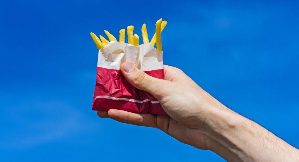 Порция картофеля фри в руке