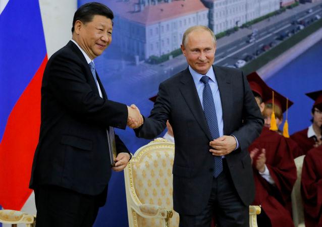 中華人民共和國主席習近平與俄羅斯總統弗拉基米爾·普京在聖彼得堡國立大學授予中國主席習近平名譽博士的慶典上握手致意