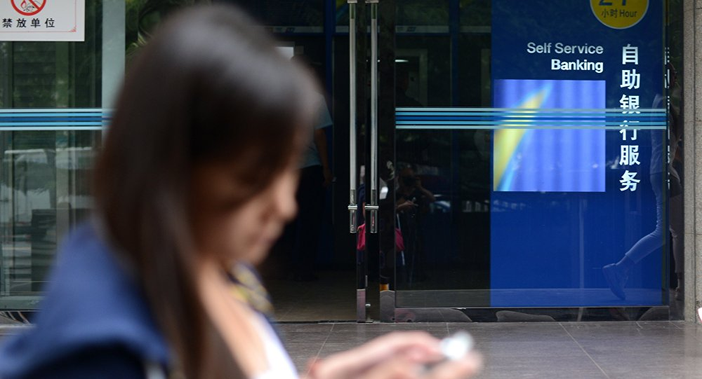 A woman looks at her mobile phone as she walks past a bank in Beijing