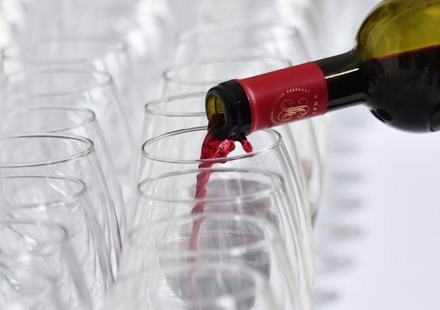 Разлив красного вина по бокалам