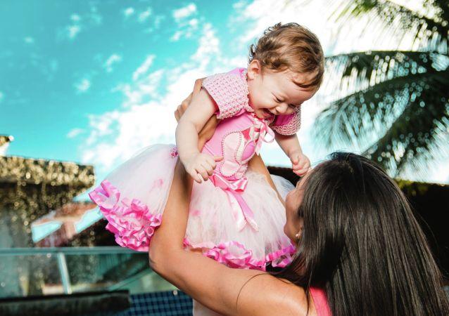 妈妈高高举起自己的女儿